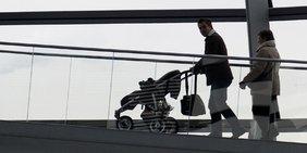 Eine junge Familie unterwegs. Vater scheibt den Kinderwagen.