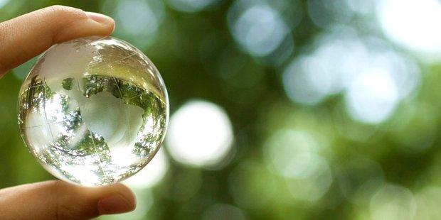 Zwei Finger halten Weltkugel aus Glas