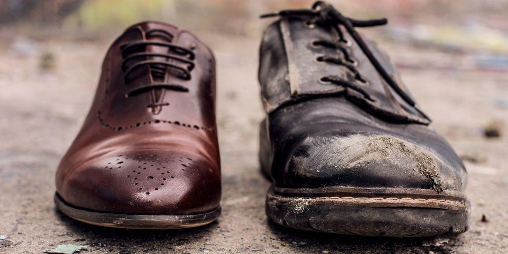 Eleganter brauner Budapester Schuh neben einem alten, schmutzigen und abgewetzten Schuh