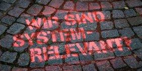 Grafitti auf Straße: Wir sind Systemrelevant