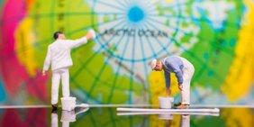 Zei Miniaturfiguren in Maler-Kleidung streichen einen Globus