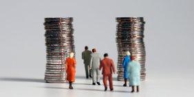 Kleine Miniatur-Figuren gehen an großen Münzstapeln vorbei