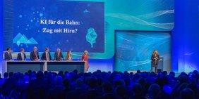 Bühne mit blauem Hintergrund; Bildschirm mit Text zu Künstlicher Intelligenz (KI) - Bild vom Digitalgipfel 2018 der Bundesregierung