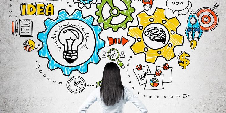 Frau steht vor Wand mit bunter Skizze mit Zahnrädern, Glühbirnen etc.