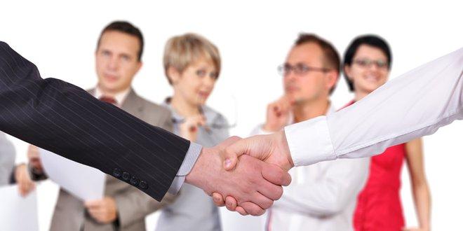 Im Vordergrund Handschlag; im Hintergrund mehrere Menschen