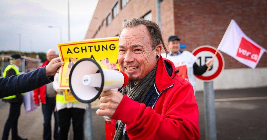 Mann mit Megafon vor ver.di-Fahne für Tarifvertrag bei Fressnapf in Krefeld