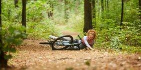 Radfahrerin mit Fahrrad hingefallen auf Straße