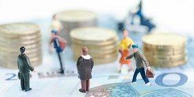 Miniaturen von Menschen zwischen Geldscheinen und Münzen