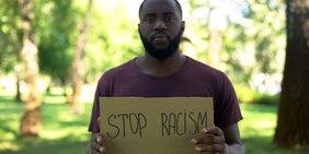 """Mann (Person of Color) hält Schild mit der Aufschrift """"STOP RACISM"""" in die Kamera"""