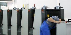 Druckereimitarbeiter bei Wartung der Druckerpressen