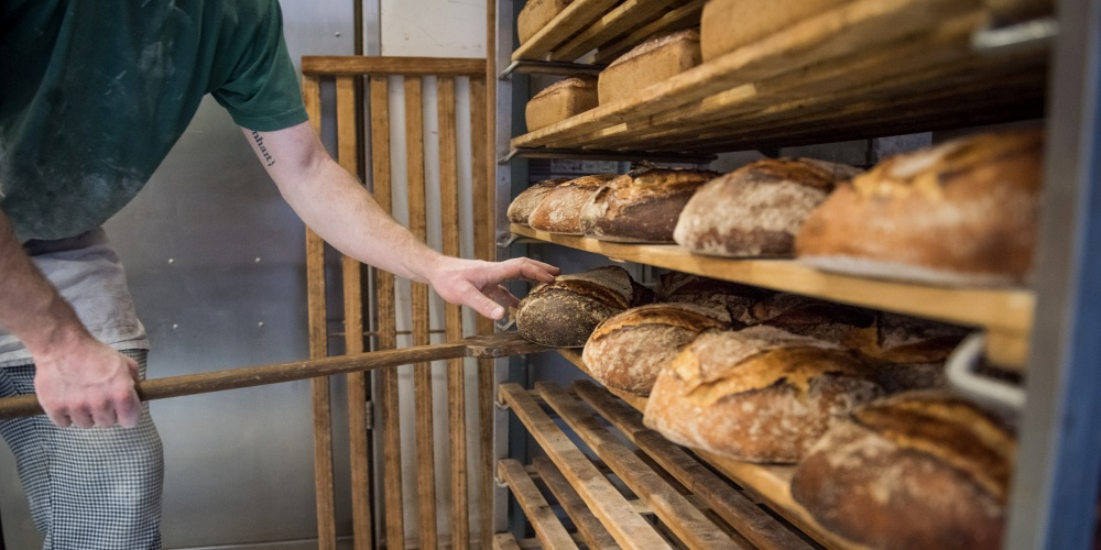 Bäcker legt Brot auf Regal zum Abkühlen