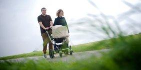 Glückliche Familie mit Kinderwagen in Landschaft