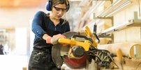Frau sägt mit Kreissäge Holz