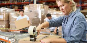 Frau klebt Karton an Fließband in Lagerhalle zu