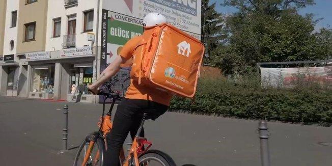 Essensauslieferer unterwegs auf dem Fahrrad mit großem orangenem Rucksack