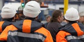 Arbeiter mit Helmen und Warnweste/-jacke
