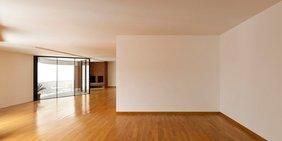 Leere Wohnung mit Parkettboden und Panoramafenstern