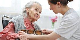 Ältere Dame im Rollstuhl mit weiblicher Pflegekraft