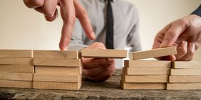 Hände bauen eine Brücke aus Holzklötzen