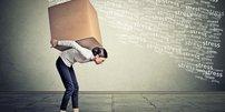 """Junge, gebückte Frau trägt großen Karton auf dem Rücken, Schriftwolke """"Stress"""""""