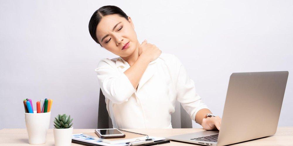 junge Frau sitzt am Laptop im Homeoffice und fasst sich mit schmerzverzerrtem Gesicht an den Nacken