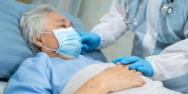 Alte Frau mit Mund-Nasen-Schutz in Krankenhaus-Bett; Hände von Arzt/Ärztin mit Kittel und Stetoskop