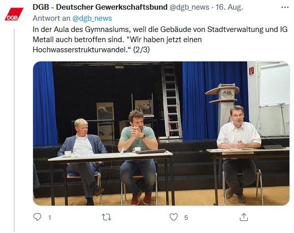 Ein Foto von Reiner Hoffmanns Sommerreise aus der Stadt Stolberg. Reiner Hoffmann sitzt mit zwei Bewohnern der Stadt auf einem Stuhl in der Aula des städtischen Gymnasiums.