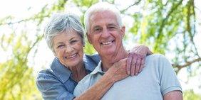 lachendes älteres Pärchen stehen sich umarmend unter einem Baum
