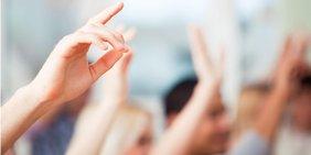 Hände nach oben strecken, sich meldende Menschen