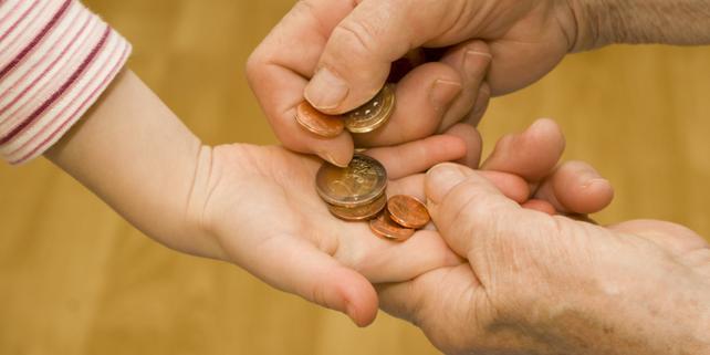 Hände von Kind und Erwachsendem mit Münzgeld