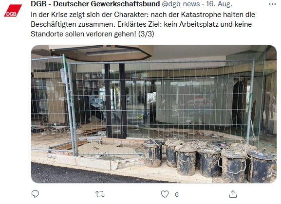 Foto vom DGB und Reiner Hoffmanns Sommerreise in Stolberg. Bauzaun der den Zutritt zu einem Gebäude versperrt, davor stehen viele Eimer mit Schlamm.