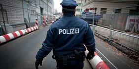 Ein Polizist läuft auf einer abgesperrten Straße.