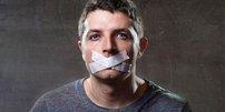 Junger Mann mit Klebestreifen über dem Mund