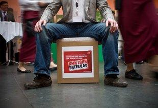 Mann sitzt auf Kiste mit dem Logo der Kampagne Deutschland braucht den Mindestlohn.