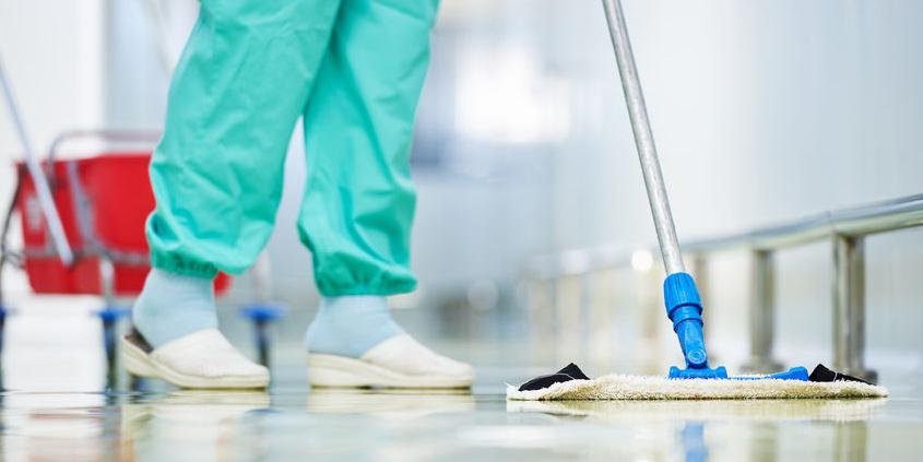 Reinigungskraft wischt Flur im Krankenhaus