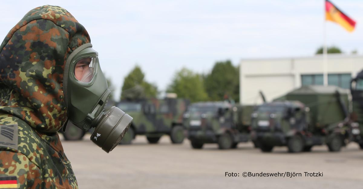 Bundeswehrsoldat mit Gasmaske vor Einsatzfahrzeugen