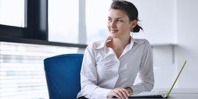 junge Frau in weißer Bluse sitzt an einem Tisch mit aufgeklappten Laptop und schaut aus dem Bild heraus