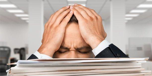 Verzweifelter Mann im Büro hinter Aktenbergen