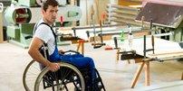 Mann im Blaumann und Rollstuhl in einer Werkstatt