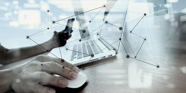 Männlcihe Hand am Laptop mit eingeblendetem Netzwerk-Diagramm