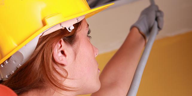 Frau mit Bauhelm verlegt Kabel, Handwerkerin, Elektrikerin, Bauarbeiterin