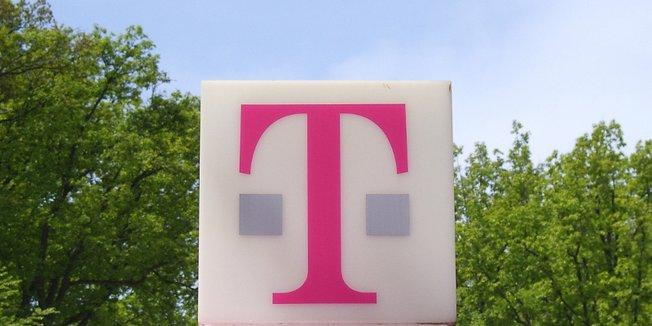 Schild mit Firmenlogo der Deutschen Telekom; Hinteregrund: Parkanlage mit Bäumen