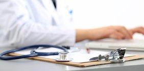 Schreibtisch mit Stethoskop und Kladde, Hände und Arm Ärztin nah