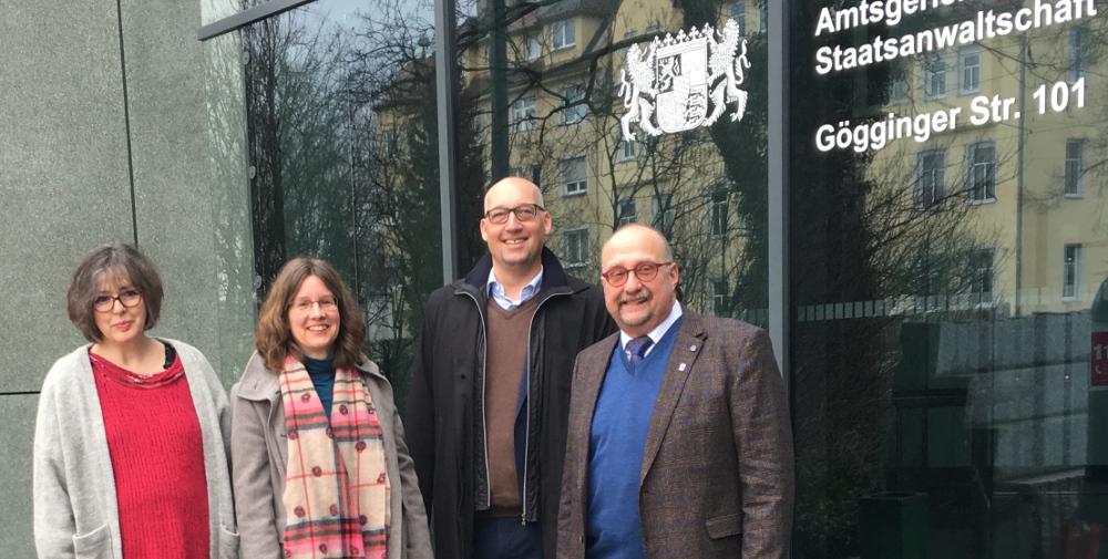 """Vier Personen (zwei Männer, zwei Frauen; Blick in die Kamera) vor einer Glassfassade mit der Aufschrift """"Staatsanwaltschaft"""" und einem Wappen des Freistaats Bayern"""