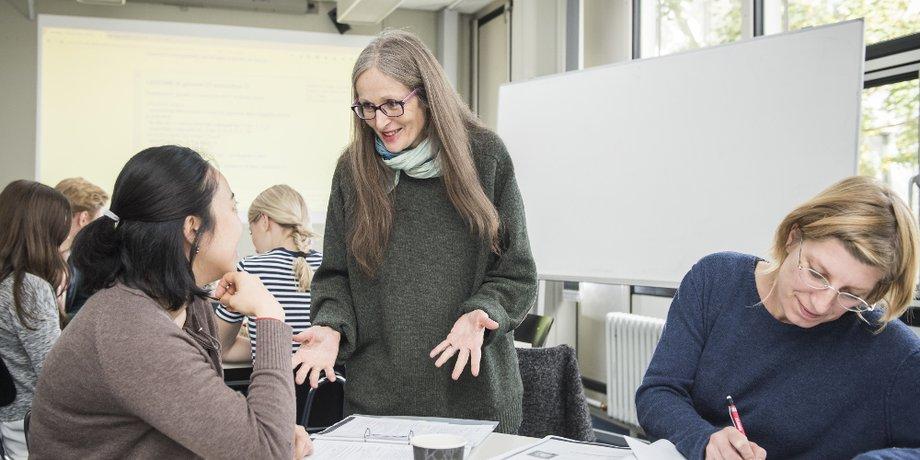 Frau mit grauen langen Haaren steht an Tisch; Gestik/Mimik zeigt: sie erläutert etwas; am Tisch sitzen zwei jüngere Frauen; Hintergrund: Seminarraum