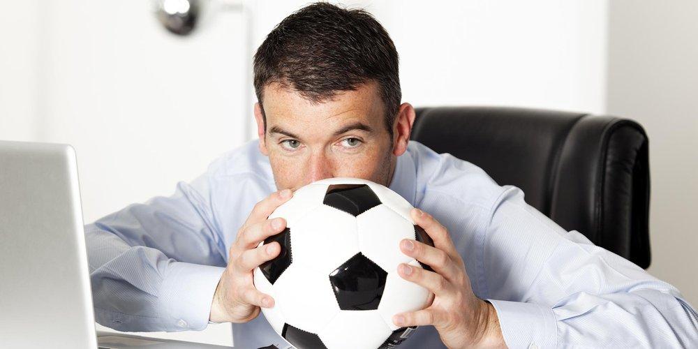 Mann am Schreibtisch mit Fußball