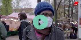 Dunkelhäutiger Mann mit Maske bei Straßenumfrage zu Bildungsinvestitionen auf dem Boxhagener Platz in Berlin