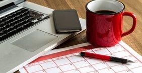 Laptop. Handy, Kalender, Stift und Kaffeetasse auf Schreibtisch