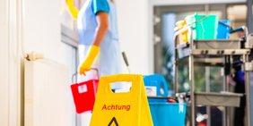 """Reinigungskraft bei der Arbeit und Warnschild """"Rutschgefahr"""""""