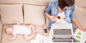 Frau mit Baby, Laptop, Unterlagen und Kaffetasse auf dem Sofa
